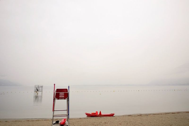 Lifeguard chair at beach against sky during foggy weather