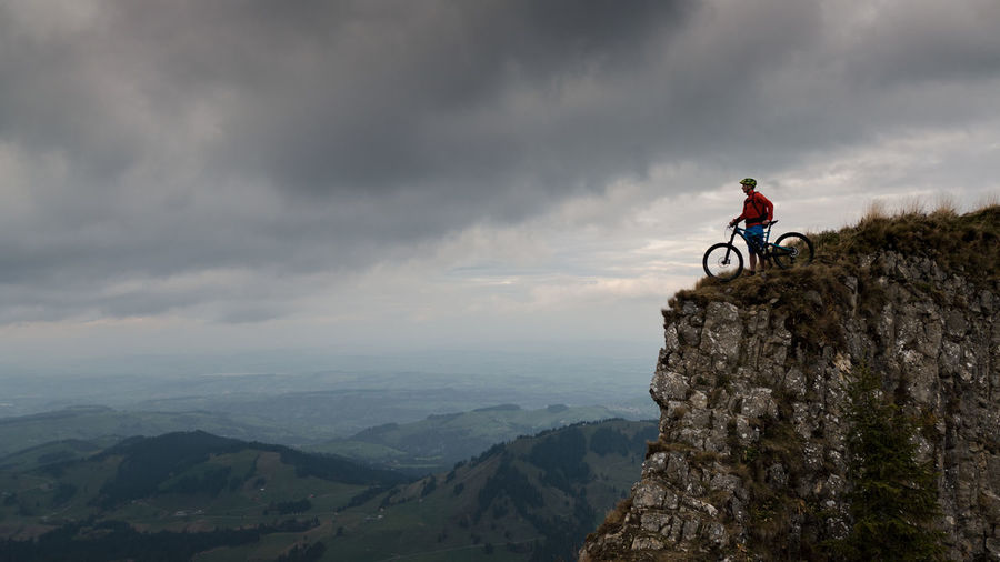 Man with bicycle on mountain against cloudy sky