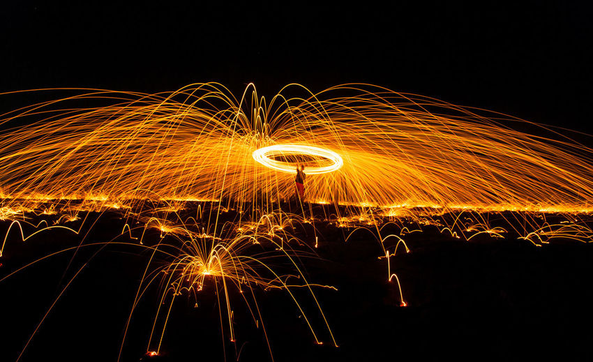 Steel Wool in Indonesia Night Motion Illuminated Wire Wool Blurred Motion Long Exposure Glowing Spinning One Person Real People Burning Sparks Orange Color Fire Lifestyles Warning Sign Nature Sign Communication Fire - Natural Phenomenon Light Trail Outdoors Dark Light