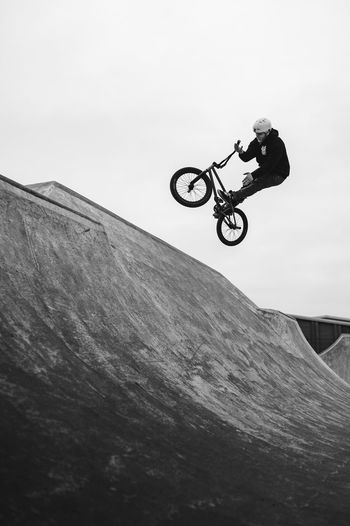 Low angle view of man jumping bicycle against sky