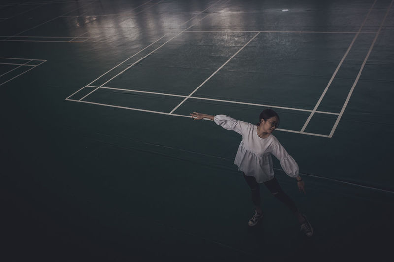 High angle view of young woman dancing on court at night