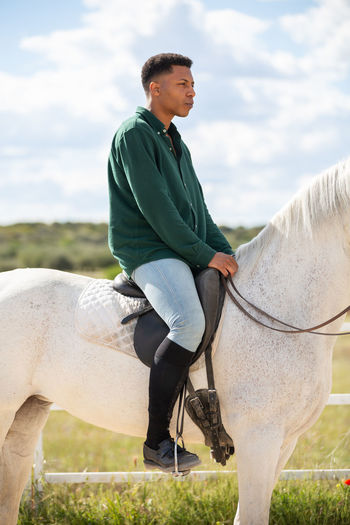 Side view of a man riding horse on field