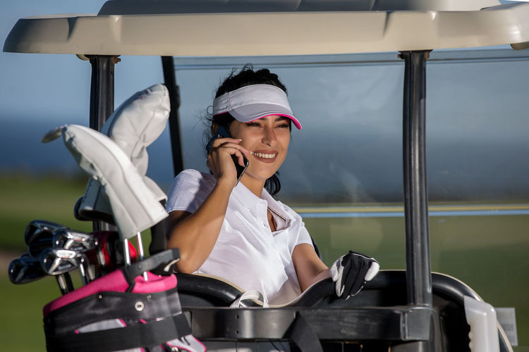 Woman Sitting In Golf Cart On Field During Sunny Day