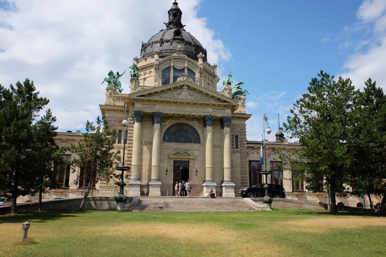 One of Main Ornate Entrances of Szechenyi Baths (designed by Gyozo Cziegler & Eve Dvorzsak, built 1902 - 1913) Blue Sky White Clouds Budapest Composition Grass Hungary Main Entrance Ornate Stonework Széchenyi Baths Tourist Attraction  Trees Architectural Columns Architecture Bronze Statues Building Exterior Building Facade Built Structure Capital City Dome Full Frame History No People Outdoor Photography Sunlight And Shadows Travel Destination