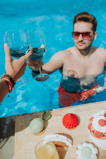 Midsection of man holding ice cream in swimming pool