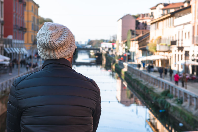 Rear view of man looking at canal