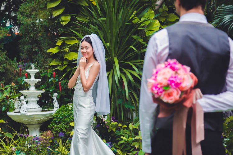 Groom hiding flowers while bride waiting against plants