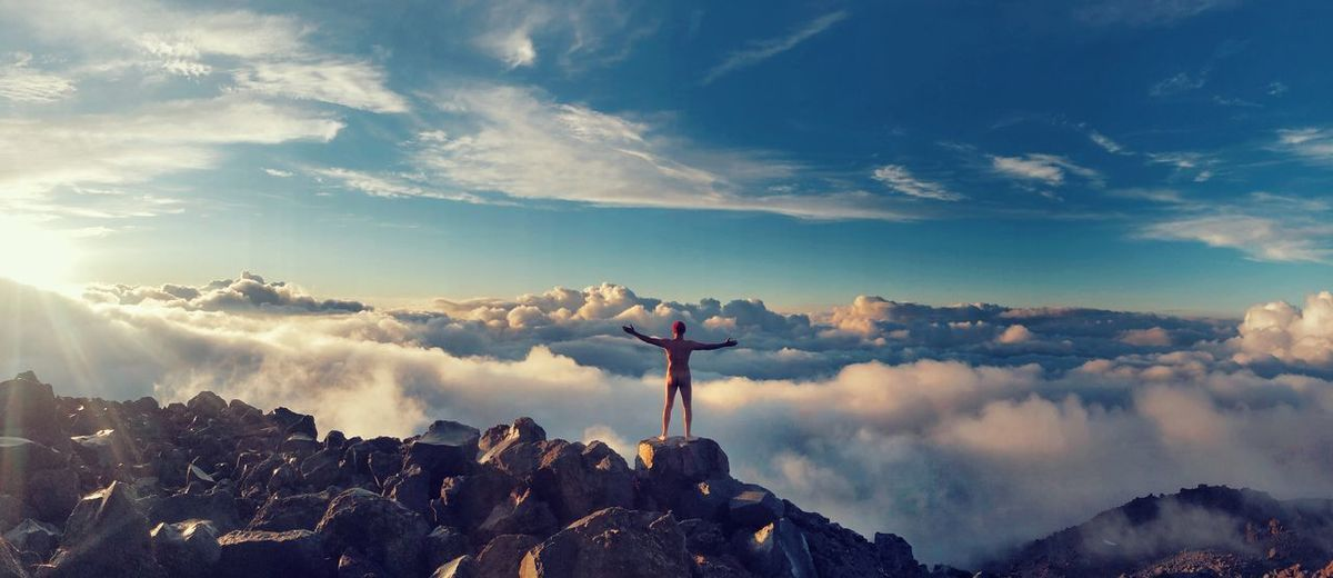 Rear view of naked man with arms outstretched looking at cloudscape
