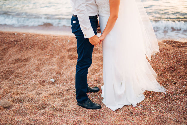 Low section of couple holding hands at beach
