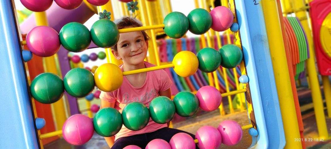 Portrait of happy girl playing with colorful balloons