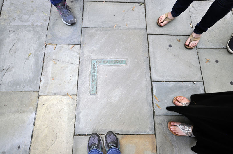 A street marker in Philadelphia, Pennsylvania. Low Section Human Leg Shoe Real People Standing High Angle View Human Body Part Men Body Part People Footpath Day Lifestyles Leisure Activity Friendship Togetherness Adult Human Foot Outdoors Flooring Tiled Floor Paving Stone Human Limb Stone Marker Street Marker