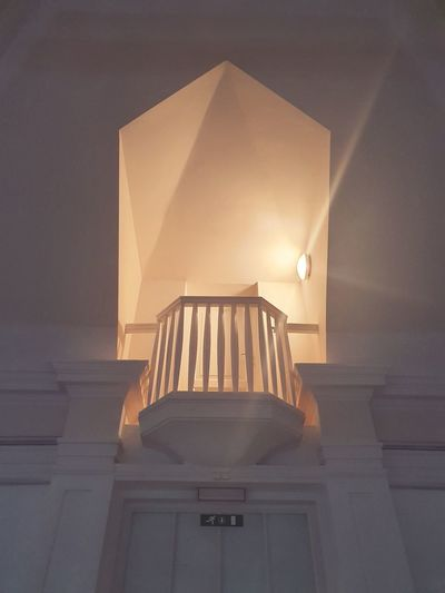 Low angle view of illuminated lamp against building