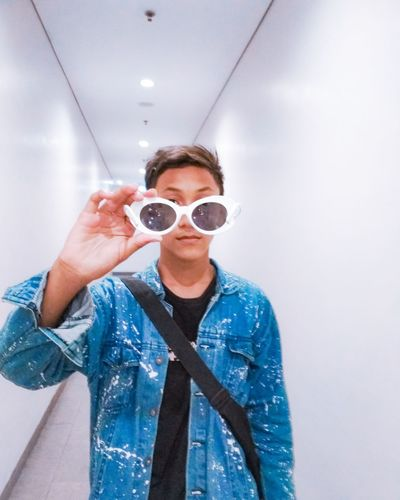 Young man holding sunglasses while standing amidst white wall