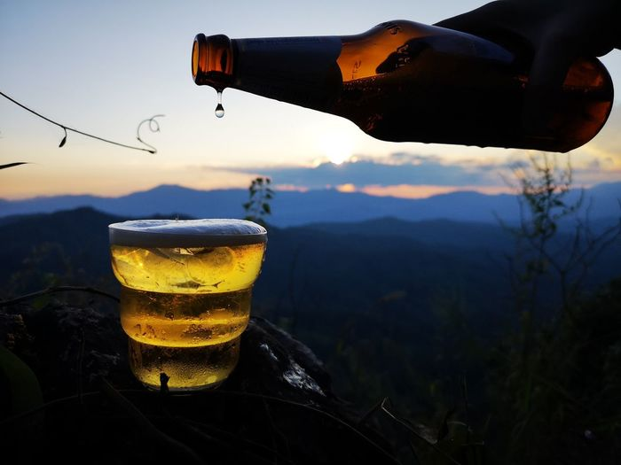 Close-up of beer glass against mountains during sunset