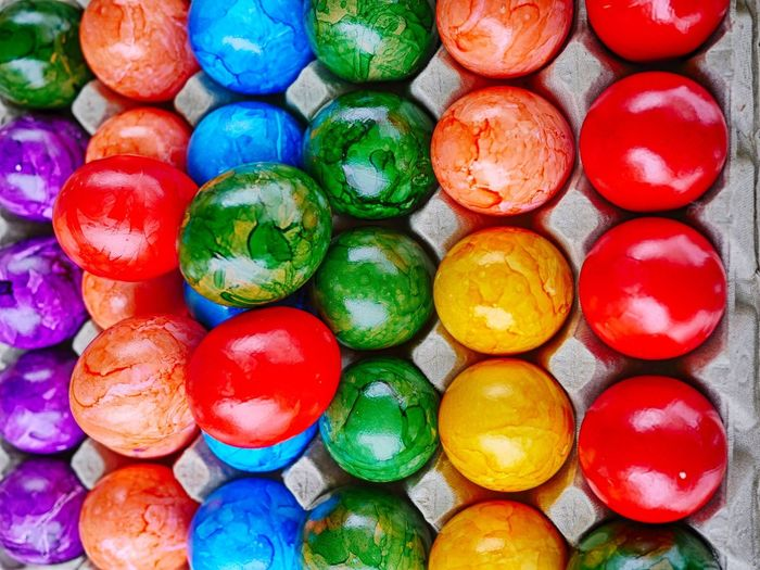 Directly above shot of colorful painted easter eggs in carton