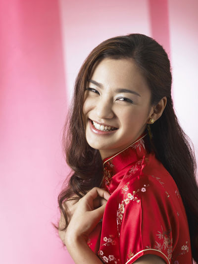 chinese woman wearing red cheongsam Red Happiness Laughing Tradition Traditional Clothing Woman Beautiful Woman Cheerful Chinese Chinese New Year Cultural Festival Gong Xi Fa Chai Happiness Lifestyles Long Hair Looking At Camera One Person Oriental Style People Qipao Smile Toothy Smile Traditional Costume Wearing