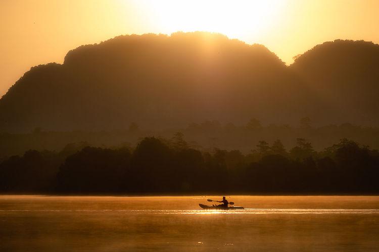 Silhouette people on boat against orange sky