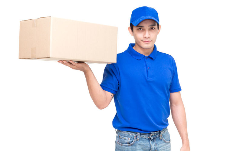 Portrait of salesman with cardboard box standing against white background