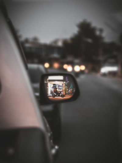 Reflection of man photographing car on windshield