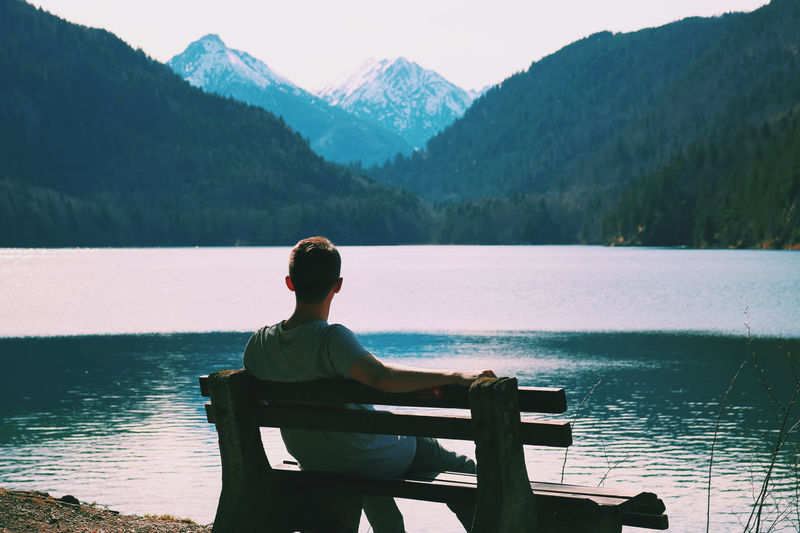 Rear view of man sitting by lake against mountains