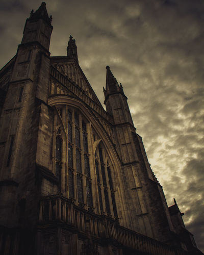 Dramatic angle of the frontage of Winchester Cathedral, Dark and Moody with bubbling skies Cathedral Dramatic Lighting Dramatic Sky Magnificent Spooky Atmosphere Winchester Architecture Building Exterior Built Structure Cloud - Sky Day History Low Angle View No People Outdoors Place Of Worship Religion Sky Spirituality Spooky Sunset