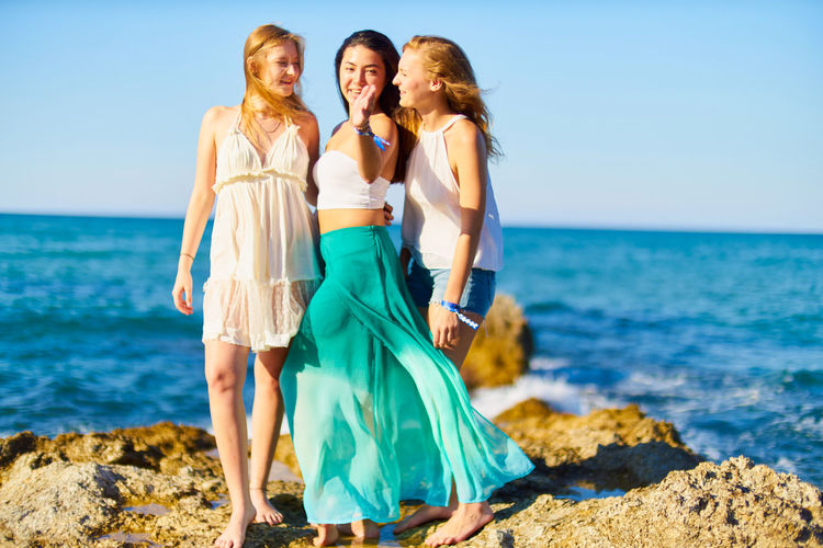 Female friends standing on rock against sea during sunny day