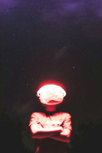 Digital composite image of person holding illuminated light against black background