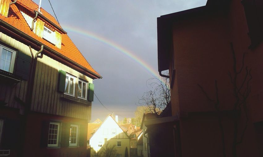 Low angle view of rainbow over houses