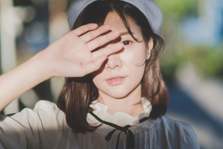 Close-up portrait of young woman shielding eyes on sunny day