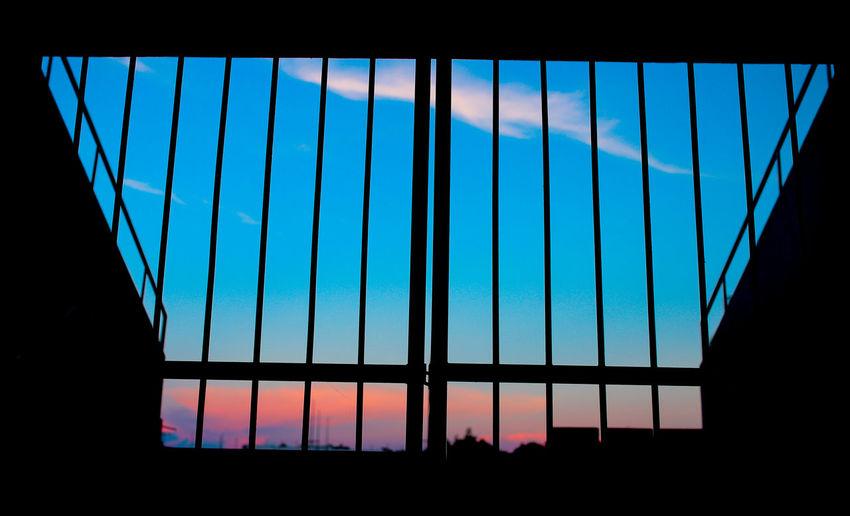 Imprisonment Architecture Blue Built Structure Cloud - Sky Dusk Grilled Imprisonment Indoors  No People Reflection Silhouette Sky Sunset Window