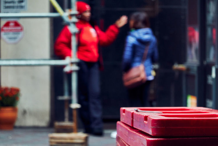 Close-up of red stacked pallets against female friends standing on footpath