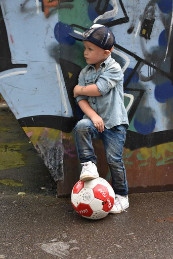 Boy with ball standing in park