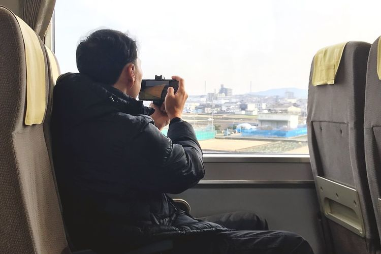 on the train Take A Photo Asian Man Tourist Travel Japan Train Real People Technology Photography Themes Sitting Communication Wireless Technology Smart Phone Photographing Mobile Phone Travel Window