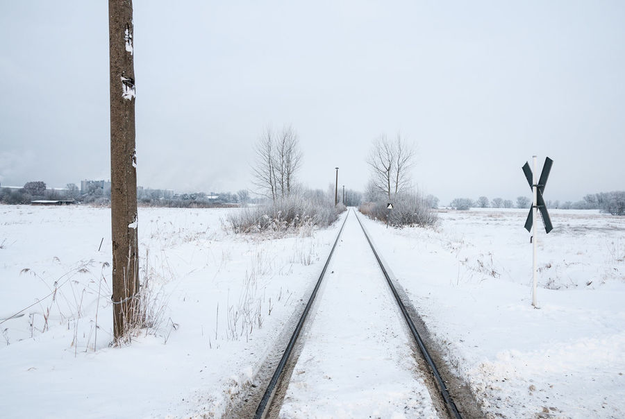 Diminishing perspective of railroad track in snow-covered landscape Bare Tree Beauty In Nature Cold Temperature Copy Space Day Diminishing Perspective Landscape Nature No People Outdoors Overcast Rail Transportation Railroad Track Remote Road Sign Rural Scene Scenics Sky Snow St. Andrew's Cross The Way Forward Tranquil Scene Tree Vanishing Point Winter