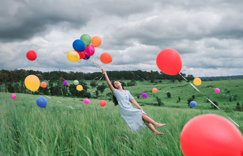 Rear view of woman with balloons on field against sky