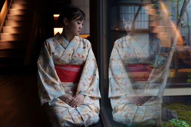 Sad Woman Wearing Traditional Clothing Looking Through Window At Home