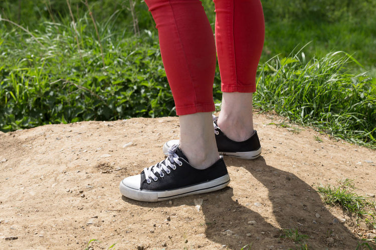 Low section of person wearing canvas shoes on sunny day