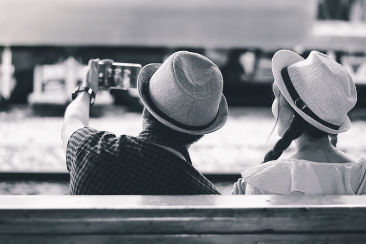 Rear view of couple doing selfie while sitting outdoors
