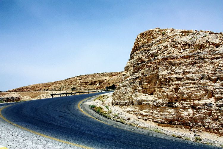 Road by rock formation against clear blue sky