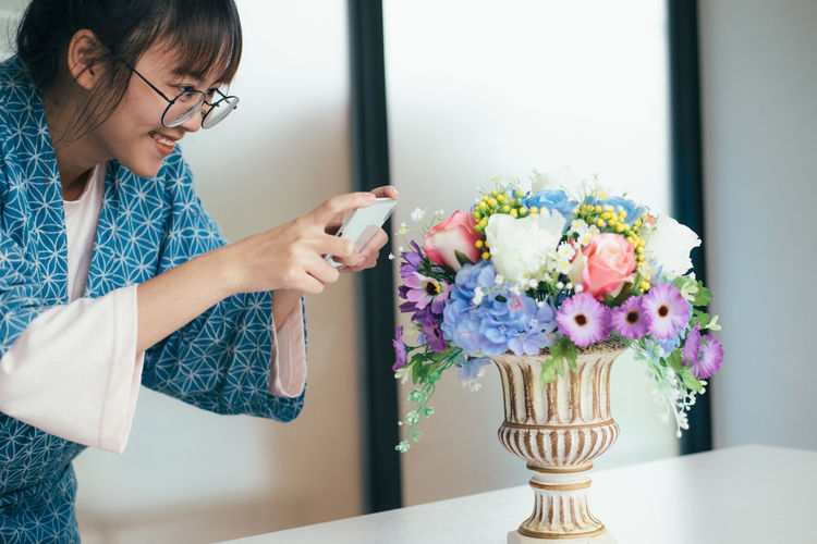 Smiling young woman photographing flowers in vase on table