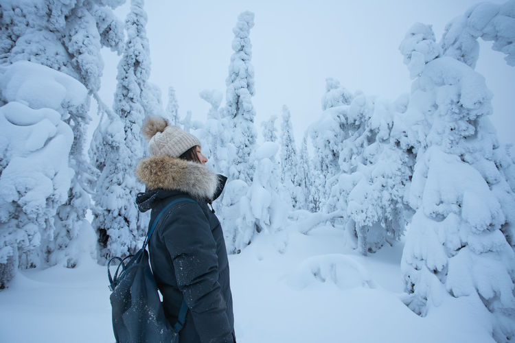 Side view of backpack woman standing amidst frozen trees during winter