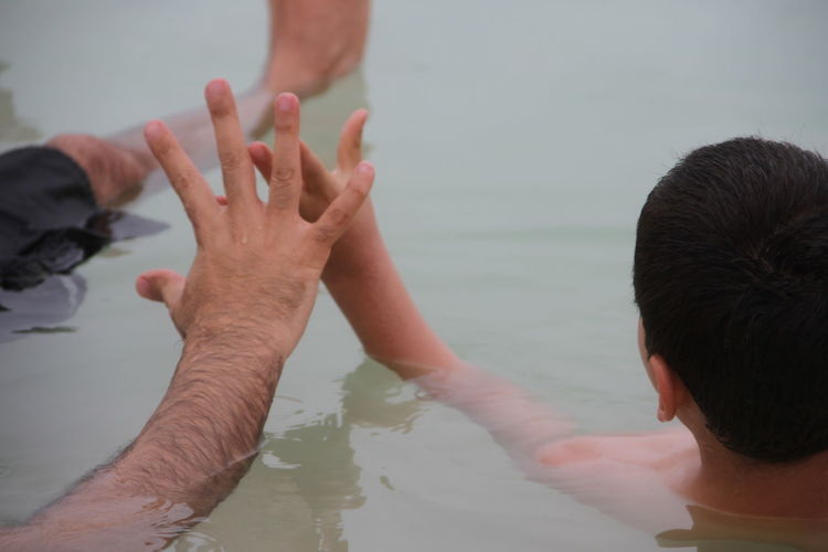 Cropped Image Of Father And Son Relaxing In Dead Sea