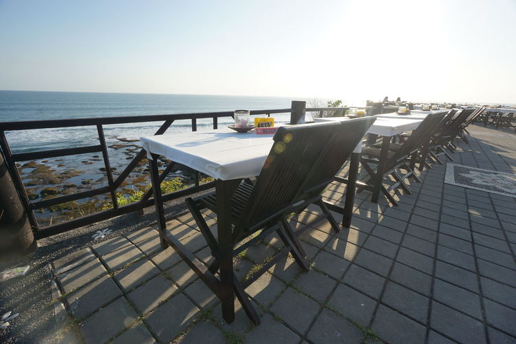 Empty chairs and tables at seaside