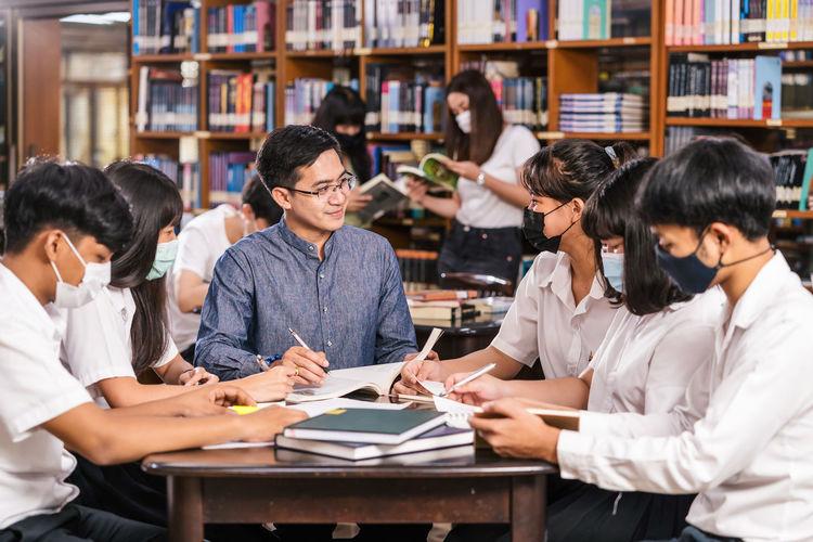 Professor teaching students wearing masks at library