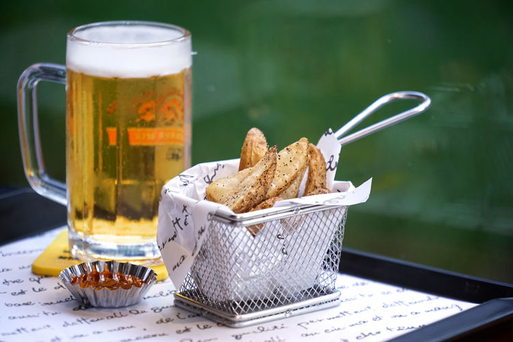 Close-up of potato wedges and beer in tray