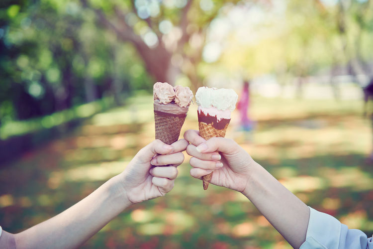 Cropped hands of people holding ice cream cones