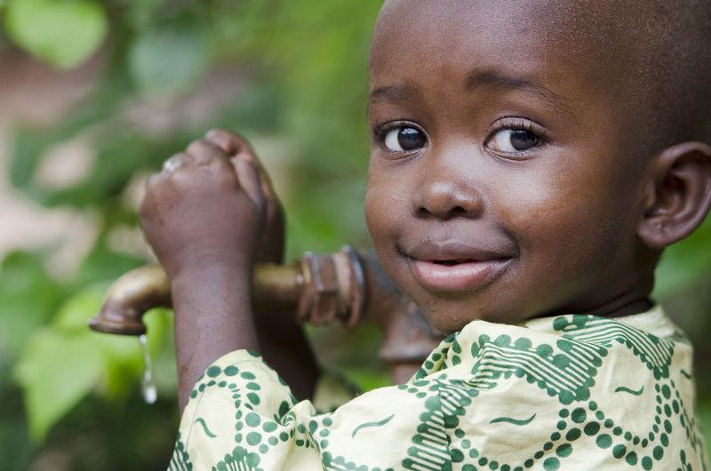 Close-up portrait of cute boy holding faucet against plants