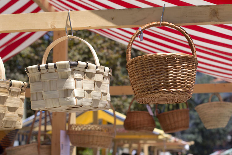 Low angle view of wicker baskets hanging at market stall