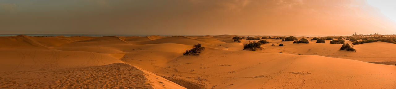 Panoramic view of desert against sky during sunset