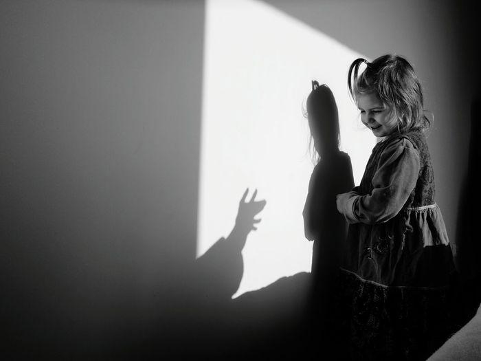 Cute girl looking at shadow on wall